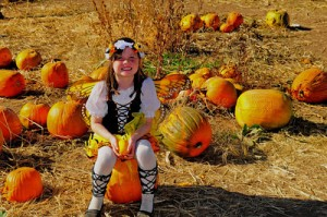 A young visitor dressed as an Autumn Fairy, sit on a pumpkin in the Pumpkin Patch at Denver Botanic Gardens at Chatfield. She is smiling and enjoying her day at the Gardens' Annual Pumpkin Festival.